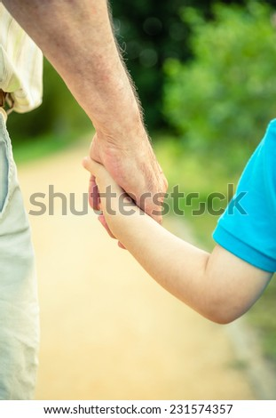 Back view of child holding hand of senior man over a nature background. Two different generations concept. - stock photo