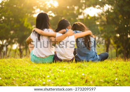 Back view of cute girls seated on green grass and relaxing - stock photo