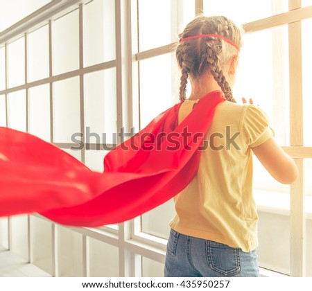 Back view of cute little girl dressed like superhero looking through the window while playing at home - stock photo