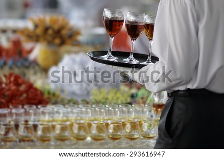Back view of elegant waiter in formal black and white clothes with serving tray with wine glasses of amber hard beverage of cognac or brandy near full buffet table, horizontal picture - stock photo