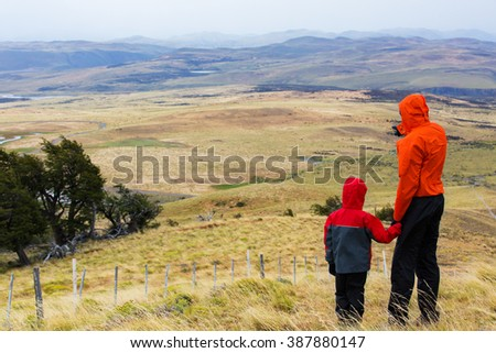 back view of family enjoying hiking in patagonia, chile - stock photo