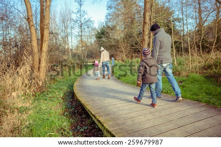 Back view of family walking together holding hands over a wooden pathway into the forest - stock photo