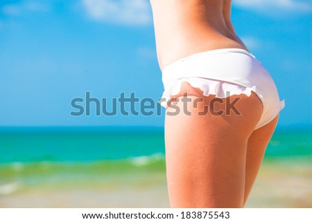 back view of fit young woman in white bikini - stock photo