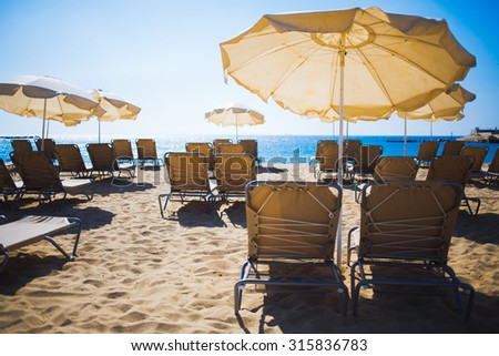 Back view of free deck chairs and sunshades on coastline against blue sky in beautiful sunny summer day, summer rest near the sea during weekend, vacation s concept - stock photo