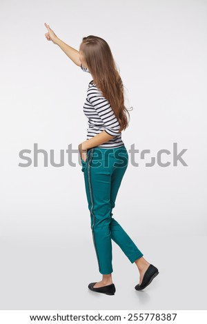 Back view of full length business woman in pointing at copy space, on gray background - stock photo