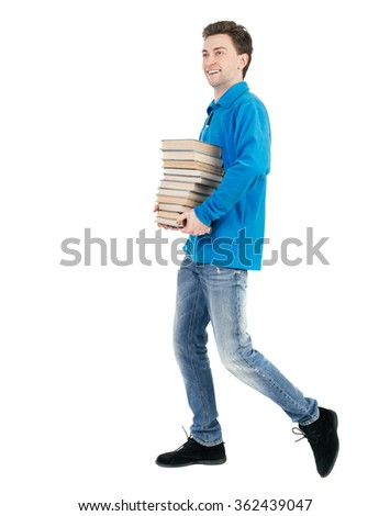 back view of going  man carries a stack of books. walking young guy . Rear view people collection.    Isolated over white background. The guy in a warm sweater carries a book with a broad smile. - stock photo