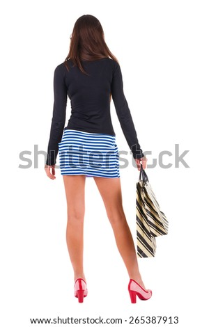 back view of going  woman  in  dress woman with shopping bags . beautiful brunette girl in motion.  backside view of person.  Rear view people collection. Isolated over white background. - stock photo