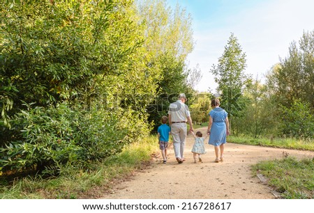Back view of grandparents and grandchildren walking on a nature path - stock photo