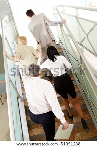 Back view of group of business people going upstairs in office building - stock photo