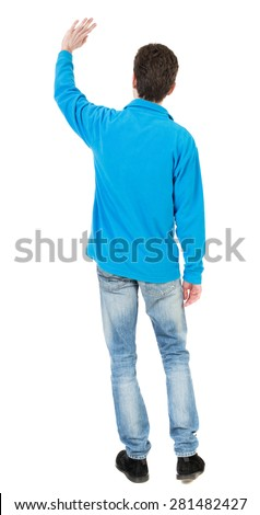 Back view of handsome man greeting waving from his hands. Standing young guy in jeans. backside view of person.  Isolated over white background.  The guy in the blue sweater waving his left hand - stock photo