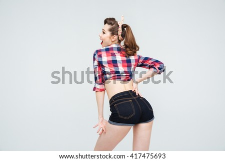 Back view of happy attractive pinup girl in checkered shirt and shorts  - stock photo