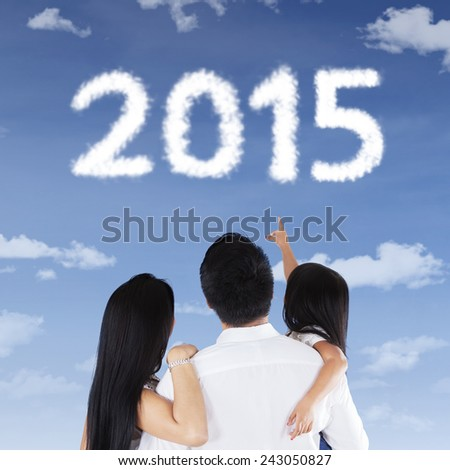 Back view of happy family looking at numbers 2015 in the sky together, shot outdoors - stock photo