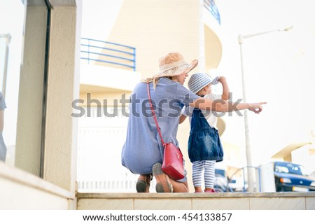Back view of happy mother and daughter pointing finger spending time together walking, outdoors background - stock photo