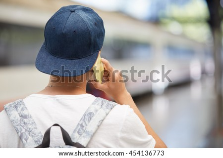 Back view of high school student boy carrying backpack going to school. Caucasian teenager in snapback making phone call while waiting his friends on the platform at the railway station. Film effect - stock photo