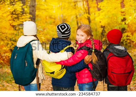Back view of kids group stand close with rucksacks - stock photo