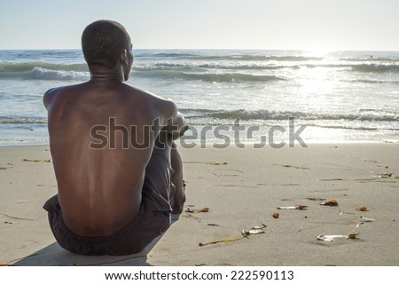 Back view of lean young shirtless African American man sitting on sand while watching waves roll in on beautiful beach under setting sun - stock photo