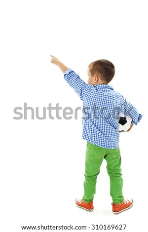 Back view of little boy holding football, points at wall. Rear view. Isolated on white background   - stock photo