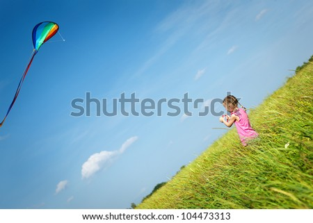 Back view of little girl flying a kite in the field - stock photo