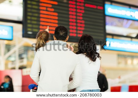 back view of little girl with her parents pointing at flight information at airport - stock photo