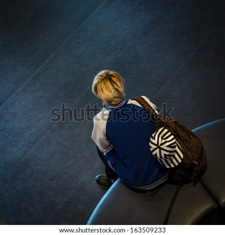 Back view of lonely teenage boy sitting on black bench - stock photo