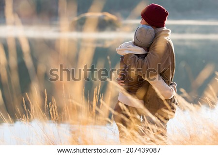 back view of lovely young couple hugging in winter - stock photo