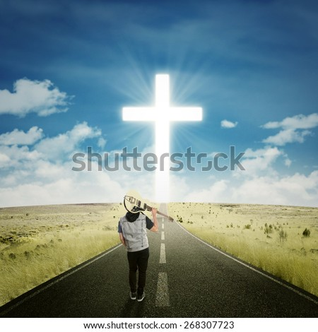 Back view of male musician carrying a guitar and walk on the road to the cross - stock photo