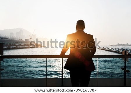 Back view of male successful entrepreneur enjoying evening sunset while standing outdoors in marina port. Silhouette of male skilled and confident businessman is thinking about his future plans - stock photo