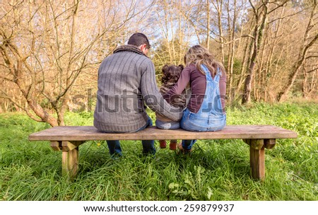 Back view of man and woman hugging to a little girl sitting on the center of a wooden bench in the park. Family leisure outdoors concept. - stock photo