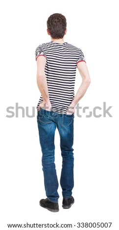 Back view of man in jeans. Standing young guy. Rear view people collection.  backside view of person.  Isolated over white background. A guy in a T-shirt is his hands in the back pockets of jeans. - stock photo