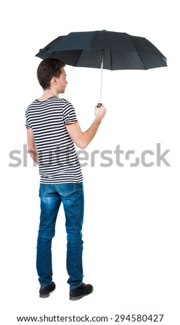 Back view of man in jeans under an umbrella. Standing young guy. Rear view people collection.   Isolated over white background. The guy in the striped shirt standing under a black umbrella. - stock photo