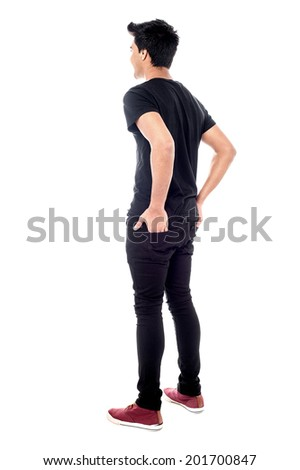 Back view of man looks ahead, hands in pocket - stock photo
