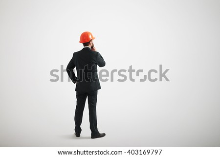 Back view of man standing straight and touching his beard wearing formal wear - stock photo
