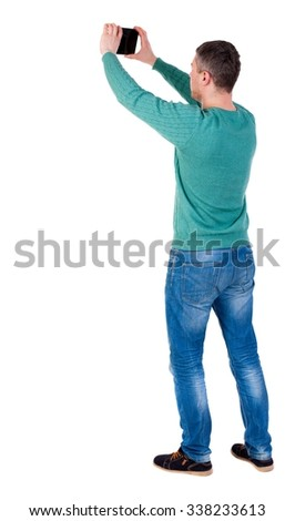 Back view of man with tablet. Standing young guy. Rear view people collection.  backside view of person.  Isolated over white background. The man in black shoes photographed object in the sky. - stock photo