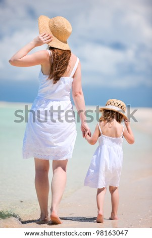 Back view of mother and daughter walking on beach - stock photo