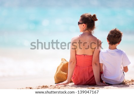 Back view of mother and son enjoying tropical beach - stock photo