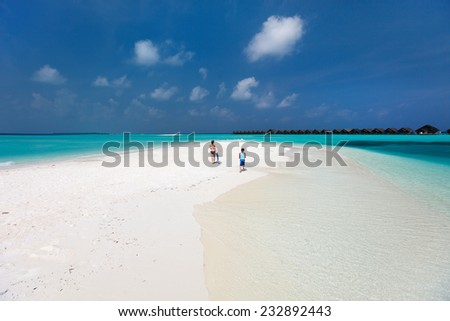 Back view of  mother and son walking at tropical beach with snorkeling equipment - stock photo