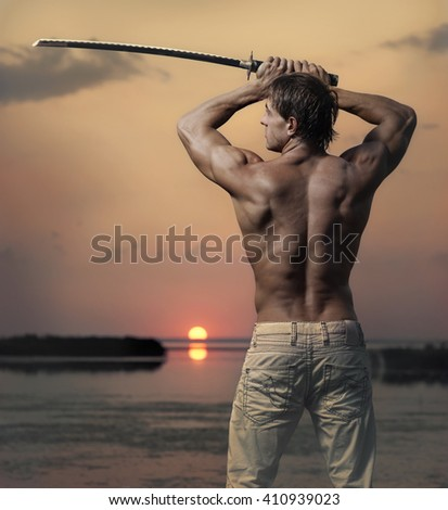 Back view of muscular handsome guy with sword at sunset - stock photo