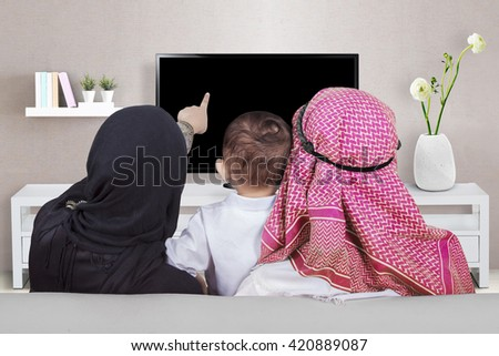 Back view of muslim family enjoy leisure time together while watching television in the living room - stock photo