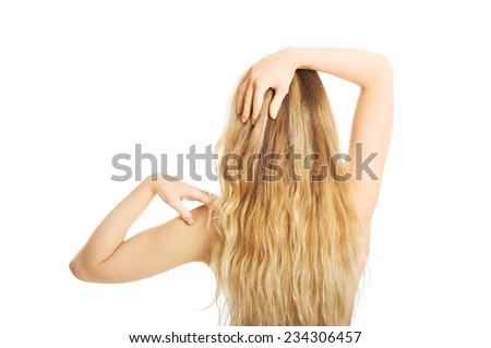 Back view of naked woman touching her shoulder. - stock photo