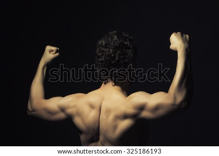Back view of one handsome sexy strong muscular young man training with bare shoulders and curly hair standing with raised hands indoor in studio on black background, horizontal picture - stock photo