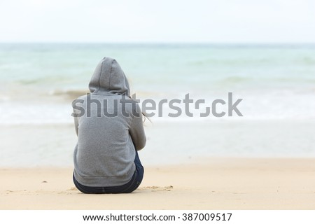 Back view of one teenager girl thinking alone and watching the sea sitting on the sand of the beach with the horizon in the background - stock photo