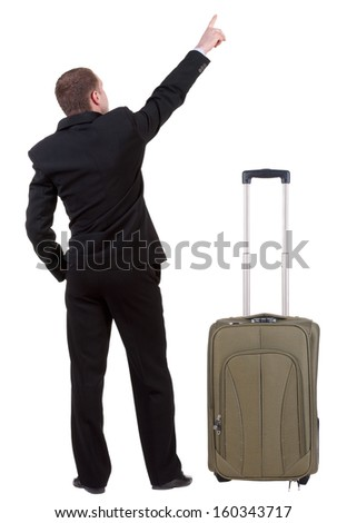 Back view of pointing business man traveling with suitcas . gesticulating young guy in black suit. Rear view people collection.  backside view of person.  Isolated over white background. - stock photo