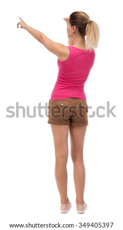 Back view of  pointing woman. beautiful girl. Rear view people collection.  backside view of person.  Isolated over white background. Blonde in brown shorts saw something interesting on the right .. - stock photo