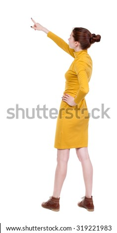 Back view of  pointing woman. beautiful girl. Rear view people collection.  Isolated over white background. Girl in mustard strict dress stands sideways resting his hand into the belt and shows up. - stock photo