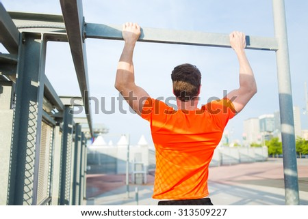 Back view of purposeful sports man with strong body engaged in active sports while pull up on the horizontal bar outdoors, young male runner in bright t-shirt training hard in urban setting at sunset - stock photo