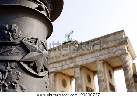 Back view of Quadriga Monument Over Brandenbourg Gate in Berlin (Germany), with in the foreground, the star of a Berlin's typical street lamp. - stock photo