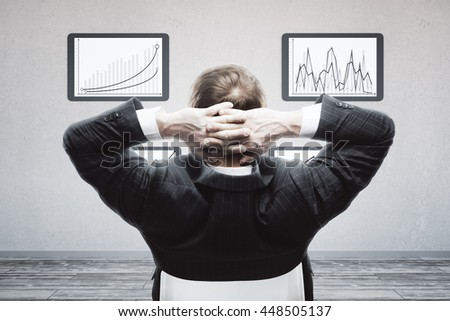 Back view of relaxing businessman with hands behind head looking at business charts in frames hanging on concrete wall - stock photo