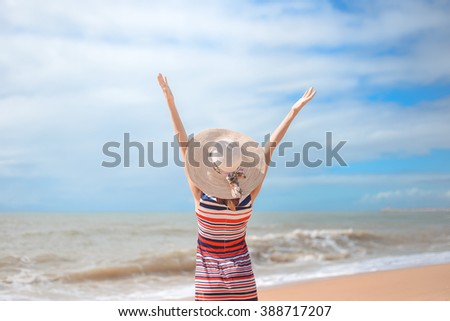 Back view of romantic lady enjoying summer beach and sun, waving at sea. Concept of feeling, freedom, pensive emotional - stock photo