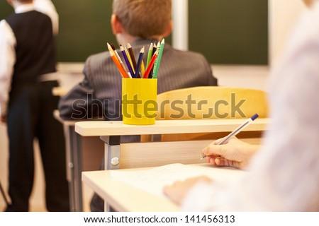 Back view of schoolchildren studying in the school - stock photo