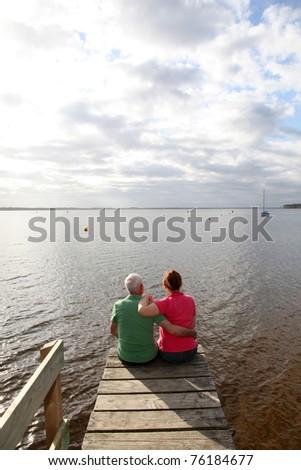 Back view of senior couple sitting on a pontoon - stock photo